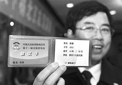 昨日,全国政协委员陈德在驻地展示刚领取的会议卡。新华社发