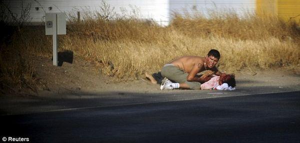 一名抢劫犯抢夺位于圣地亚哥的一家超市后被汽车撞倒。另外一名抢劫犯正在照顾他。