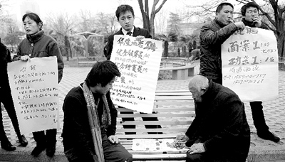 招聘现场很多人手持招聘海报却无人问津,一名招聘工作人员干脆和一位老人下起象棋。 晚报首席记者 贾俊生 图
