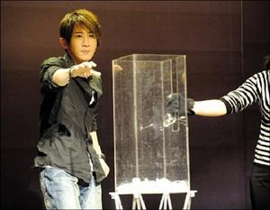 """刘谦在发布会上表演""""隔空碎杯""""。本报记者 王俭 摄"""