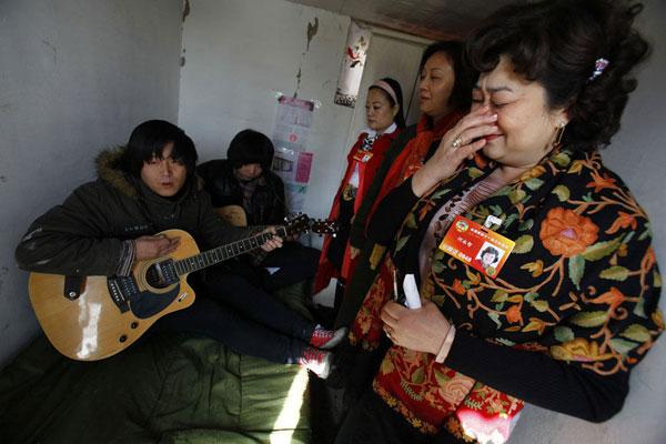 居住在唐家岭的李立国、白万龙坐在床上,演唱自己创作的《蚁族》,感动了前来看望他们的全国政协委员何永智、张礼慧、严琦(由外往里)。