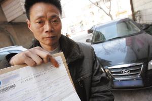老胡拿着没有保单号的假保单,到昆明找律师求助 记者 韩亿国/摄