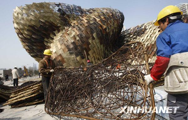 3月10日,工人正在搬运装饰西班牙馆外墙的藤条。新华社记者 裴鑫摄