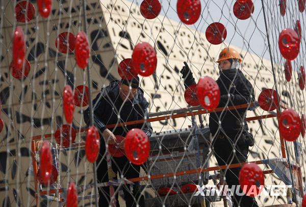 3月10日,工作人员正在为瑞士馆的外墙安装太阳能装饰照明设备。新华社记者 裴鑫摄