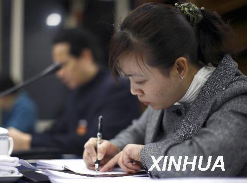 3月6日,全国人大代表胡小燕在会议上记笔记。新华社记者费茂华摄