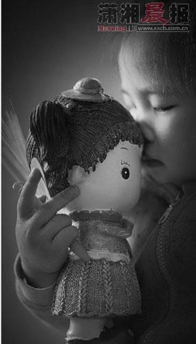 3月13日,深圳,小梦涵站在角落抱着爸爸带来的娃娃,沉浸在自己的世界中。她现在胆子特别小,很敏感,特别是碰到陌生的人。图/记者杨抒怀