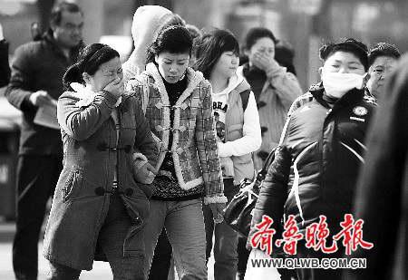 济南街头,市民在沙尘天气中行走。 王鸿光 摄