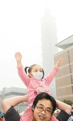 台北101大楼笼罩在沙尘之中,家长为小朋友戴上口罩。图片来源:台湾《联合报》