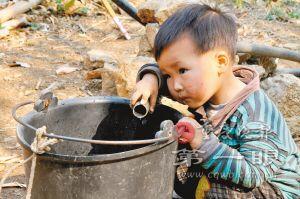 贵州省兴义市郑屯镇绒窝村王家凼组,一名小男孩拿着水管蹲在水桶旁,等着水管出水。 新华社
