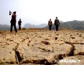 图:灾区农民下田平整土地等候降雨抢种