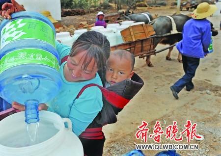 一家火锅店送来一卡车桶装水,村民将水倒入自家水桶中。本报特派记者 郭建政 摄