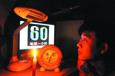 """20时31分,哈市道外区的市民张腾飞在家积极响应""""地球一小时""""熄灯活动,点燃蜡烛。 本报记者 张清云 摄"""