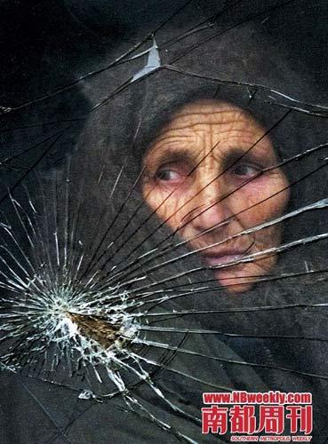 """2000年1月10日,在车臣地区的一个村庄内,一名车臣妇女透过被子弹击中的玻璃窗向外望去。由于俄罗斯与车臣数年来的战争,不少在战争中失去丈夫或儿子的妇女变身""""黑寡妇"""",发动一轮又一轮恐怖袭击。"""