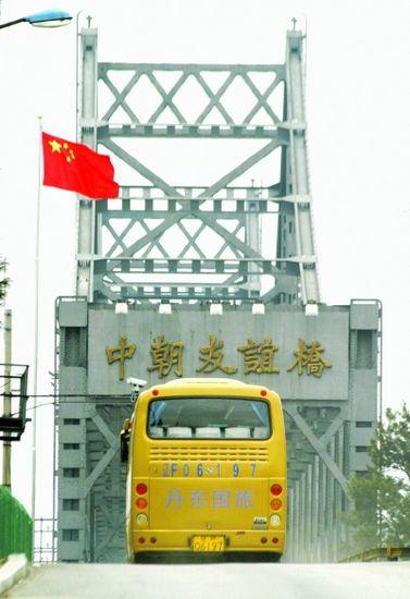 4月12日,在辽宁省丹东市中朝友谊桥附近广场,赴朝游客登上准备过境的旅游客车。
