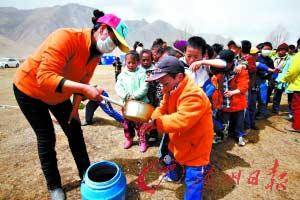 吃饭前,老师给孩子们舀水洗手。
