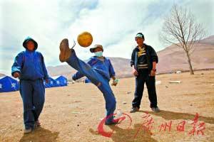 草地上,男孩子们在踢球。地震不能抹杀孩子的快乐。