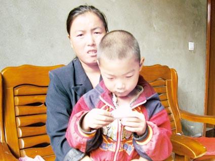2009年10月26日,死亡矿工苗建军的妻子苗瑞花紧紧搂着6岁的儿子,不愿说起丈夫死时的悲惨情景。薛子进摄(图片来源:法制日报)