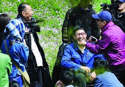张艺谋手舞足蹈地给众演员说戏,引得饰演村主任的李雪健(左上)等演员们开怀大笑