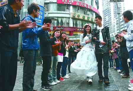 昨日,杨家坪,志愿者穿着自制婚纱走上街头宣传环保。 记者 吴珊 摄