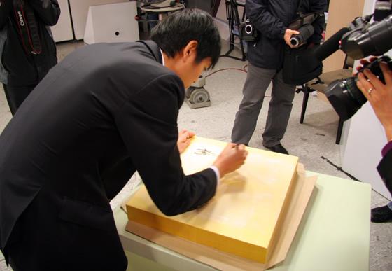图文:BC卡杯决赛第三局 李世石在棋盘上签名