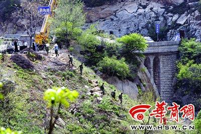 抢险人员将河中的炸药收集装袋运到公路上本报记者 赵雄韬 摄
