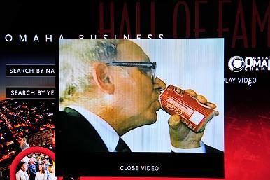 图E,奥马哈名人堂里的巴菲特纪录片,股身喝着他喜欢的而且从中收益颇丰的可口可乐