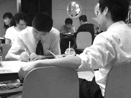 昨日中午,解放碑某快餐店内两位80后白领正在填写调查问卷 记者 王璐瑶 摄