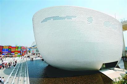 """芬兰馆""""冰壶""""宛若一座水中的岛屿,外墙上覆盖着25000片环保材料制成的鳞状物。(新华社记者 刘大伟 摄)"""