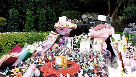 邓丽君墓前摆满了鲜花、相框和千纸鹤