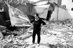 户主王女士站在自家被铲倒的房屋前。16日晚10时,朝阳雷桥村王女士家,被一辆铲车铲倒。本报记者 浦峰 摄