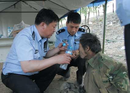 警察正在给在井下藏身多日的管道男(右一)喂食