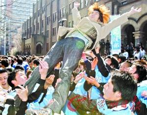 考入京都大学的日本学生被同学抛向半空,接受祝福。
