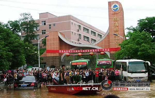 (溆浦县第一中学门口,家长们在校门等待,溆浦县民兵应急分队还在不停的转移高考考生。