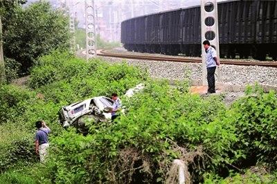 轿车撞断护栏后冲进铁路内,先后与两列火车发生撞击。本报记者朱嘉磊摄