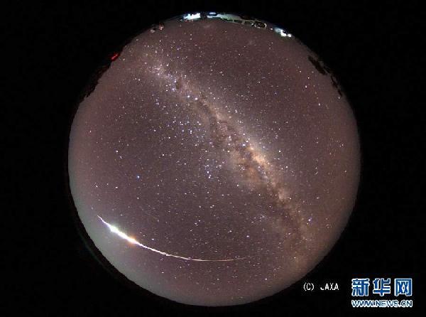 """这是6月13日在澳大利亚南部伍默拉附近的沙漠地带用鱼眼镜头拍摄的日本""""隼鸟""""号探测器的密封舱下降的图片。日本宇宙航空研究开发机构的""""隼鸟""""号小行星探测器13日夜进入大气层,降落在澳大利亚南部伍默拉附近的沙漠地带,时隔7年后回归地球。这是人类的探测器首次往返于地球和月球之外的天体。 新华社/法新"""