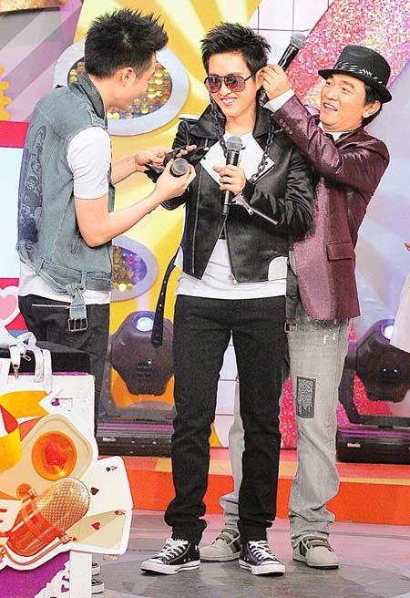 吴宗宪(右)搞笑的在黄靖伦耳上挂项链,左为周汤豪