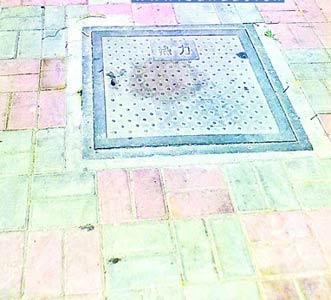 古力井盖上还留着张曾全女儿坠下楼时的污渍