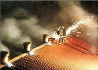 消防队员用切割机将屋顶切开释放浓烟。记者 张朋 实习生 陈冠宏 摄