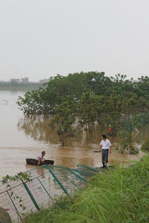 一些留守的灾民,经常划着木桶、门板,甚至是大块的泡沫塑料,出入洪涝区