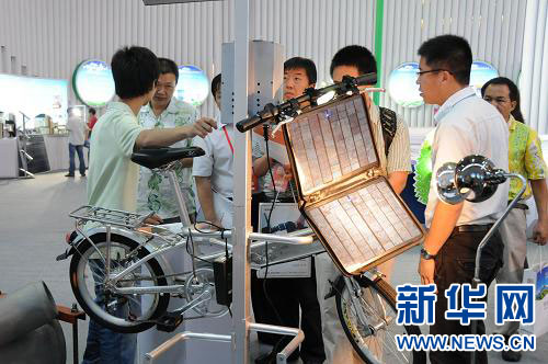 7月1日,参展商向顾客介绍环保节能的太阳能电动自行车.