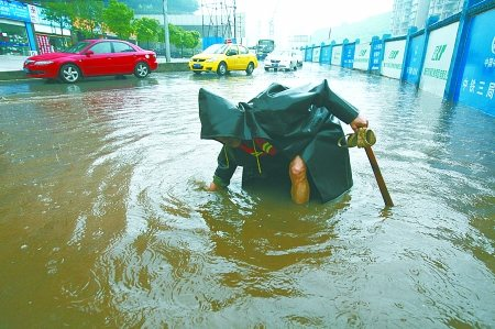 昨日,黄龙路转盘,环卫工周茂成用手在积水中摸寻窨井盖