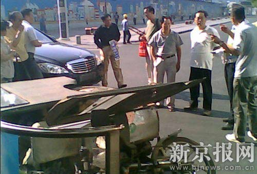 发生事故后,任志强手持奔驰车前部车牌在事故现场。读者供图