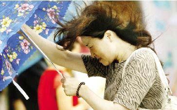 昨天下午2点,武汉街头,暴雨中的女子。本报记者 宋荣成 实习生 傅坚 摄