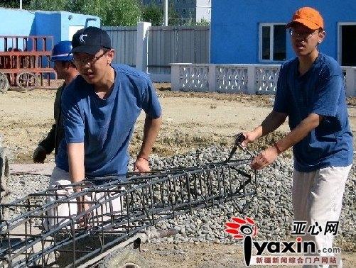左边为哥哥宋少鹏,右边为弟弟宋少栋,两人正在合力推运铁架。 通讯员 刘是何 摄