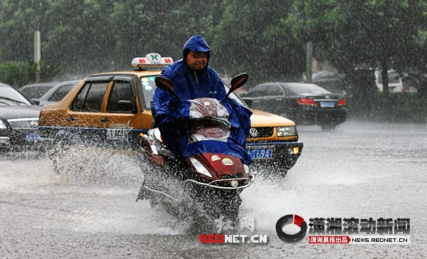 7月15日,韶山南路,一名骑电动车的市民在大雨中艰难前行,车轮压过路面积水,荡起层层浪花。