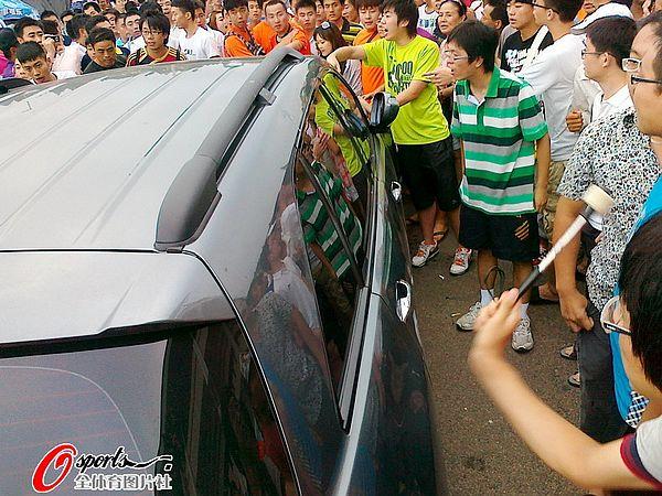 图文:[中超]青岛球迷肇事 球迷开始击打车辆