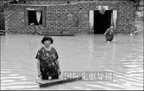 江西再次遭遇洪水侵袭、图为7月17日,该省受灾村民站在家门前等待救援。本报记者 涂超华/摄