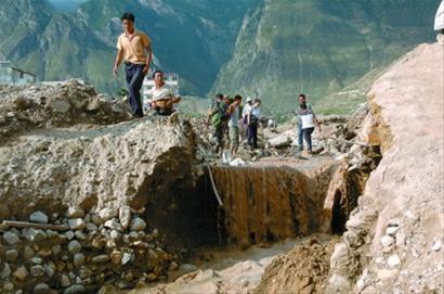 上图为在舟曲特大山洪泥石流现场,山上流下来的泥水仍然卷带着少量沙石 新华社发下图为被泥石流冲击后的舟曲县城一角 IC图片