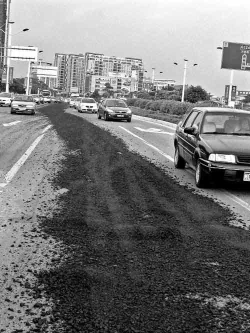 沥青洒漏一路,过往车辆避之不及。
