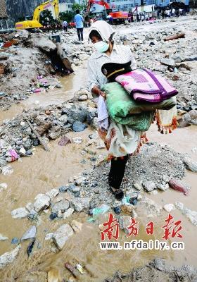 昨日,舟曲县城居民方凤菊从被冲毁的房屋里取出可用的物品。